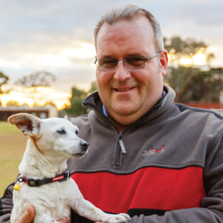 Portrait of Greg holding his small dog