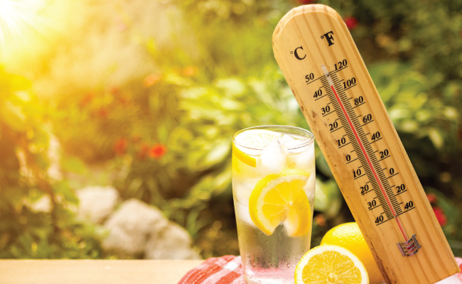 Thermometer and glass of lemon water in the heat