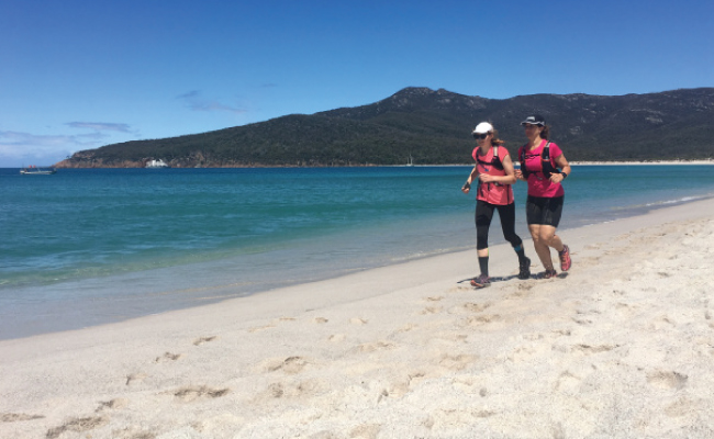 Two people running on a Tasmanian beach