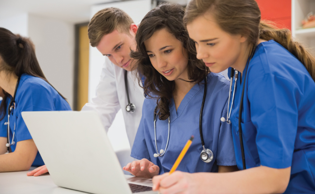 Three youth looking at laptop screen in blue medical outfits