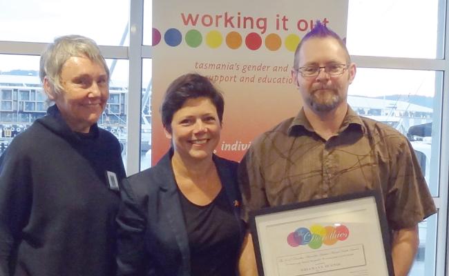Three people standing receiving an award