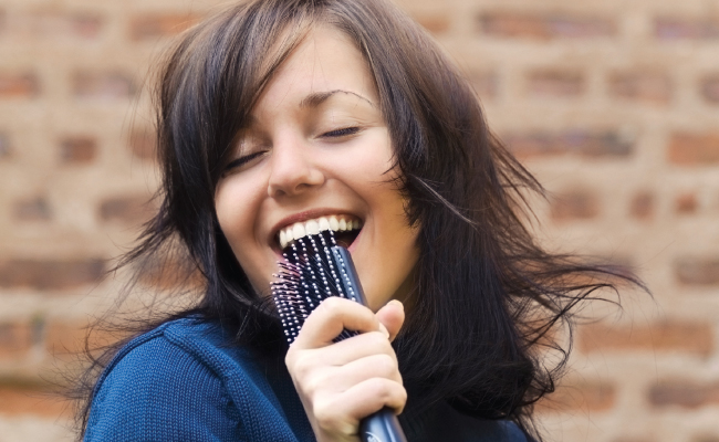 Woman singing into a hairbrush