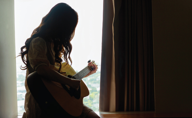 Silhouette of woman playing guitar by a window