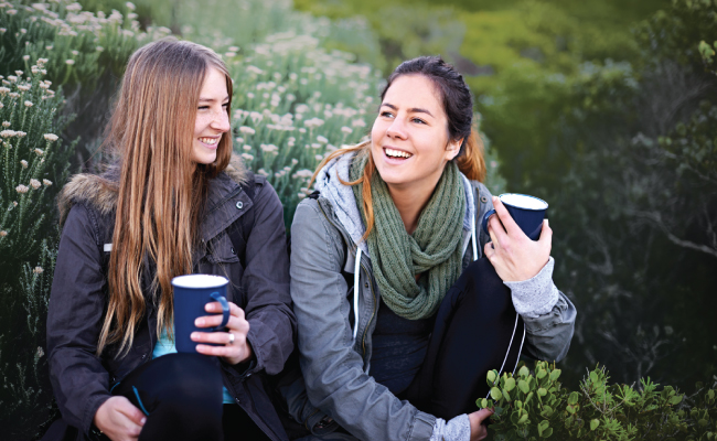 Two young women sitting outside having coffee