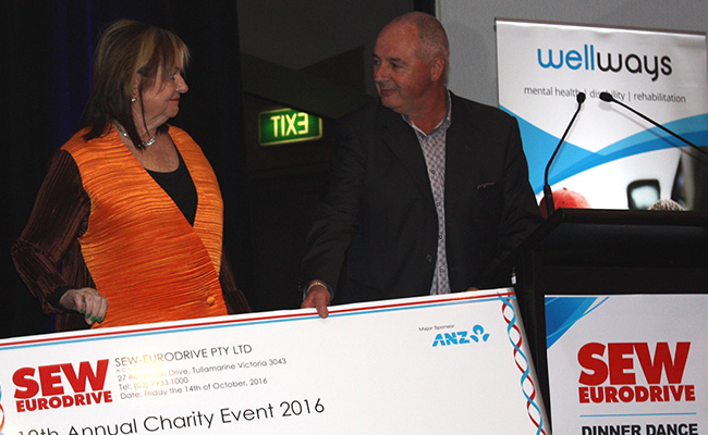 Wellways CEO Elizabeth Crowther receiving cheque from SEW EURODRIVE