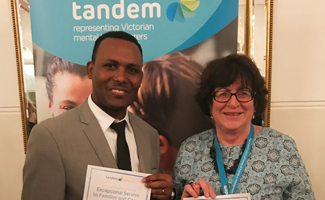 Man and woman holding certificates at Tandem Awards