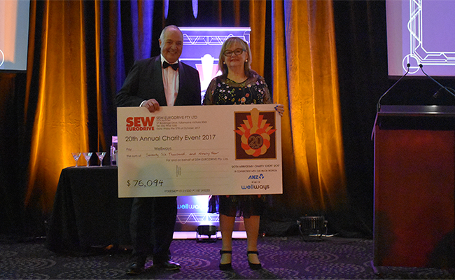 Wellways CEO Elizabeth Crowther receiving a cheque from SEW-EURODRIVE