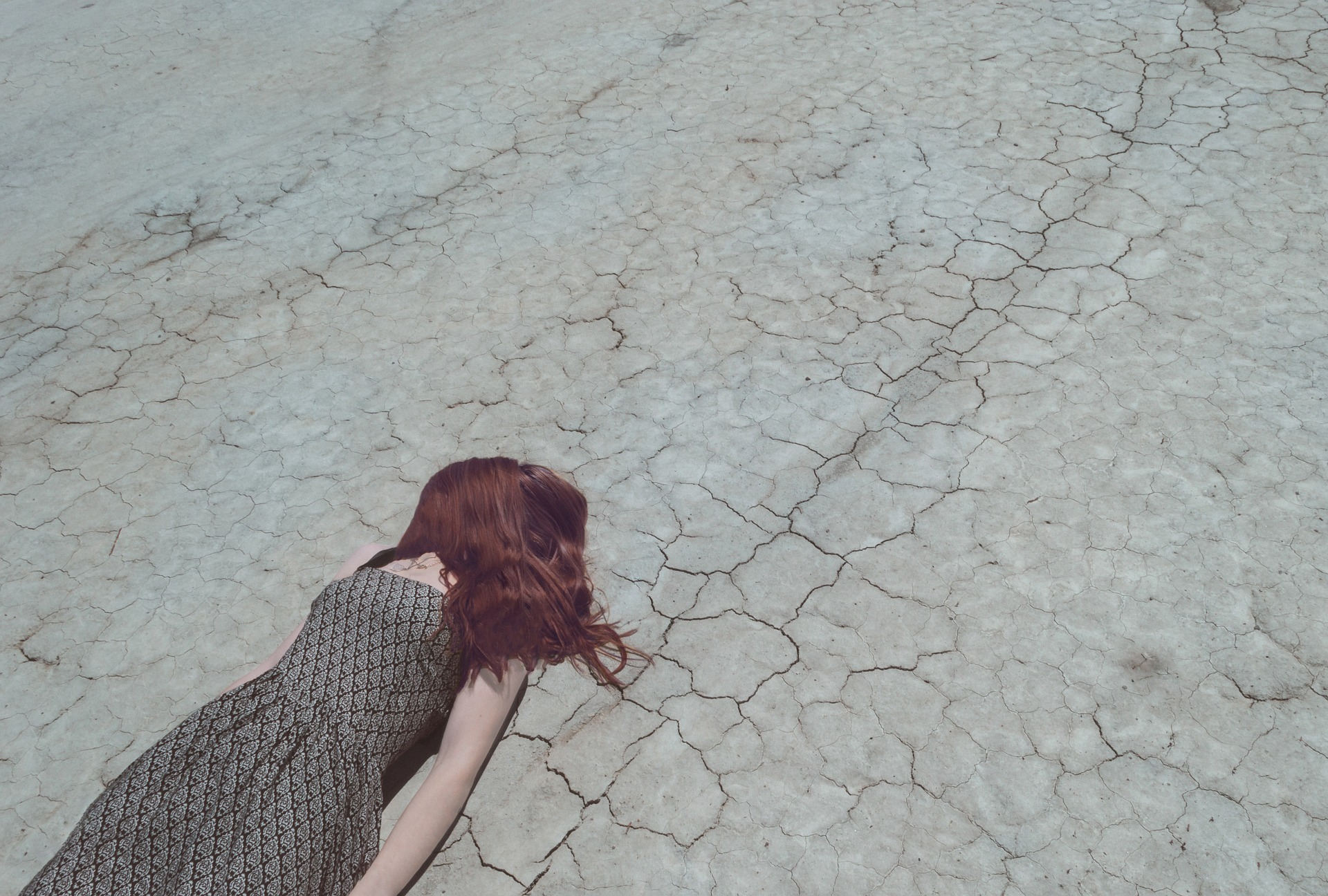 Women with mental illness laying on cracked dirt with her hair over her face