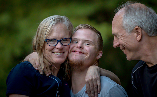 Photo of a mother and father with their son, who is living with a disability