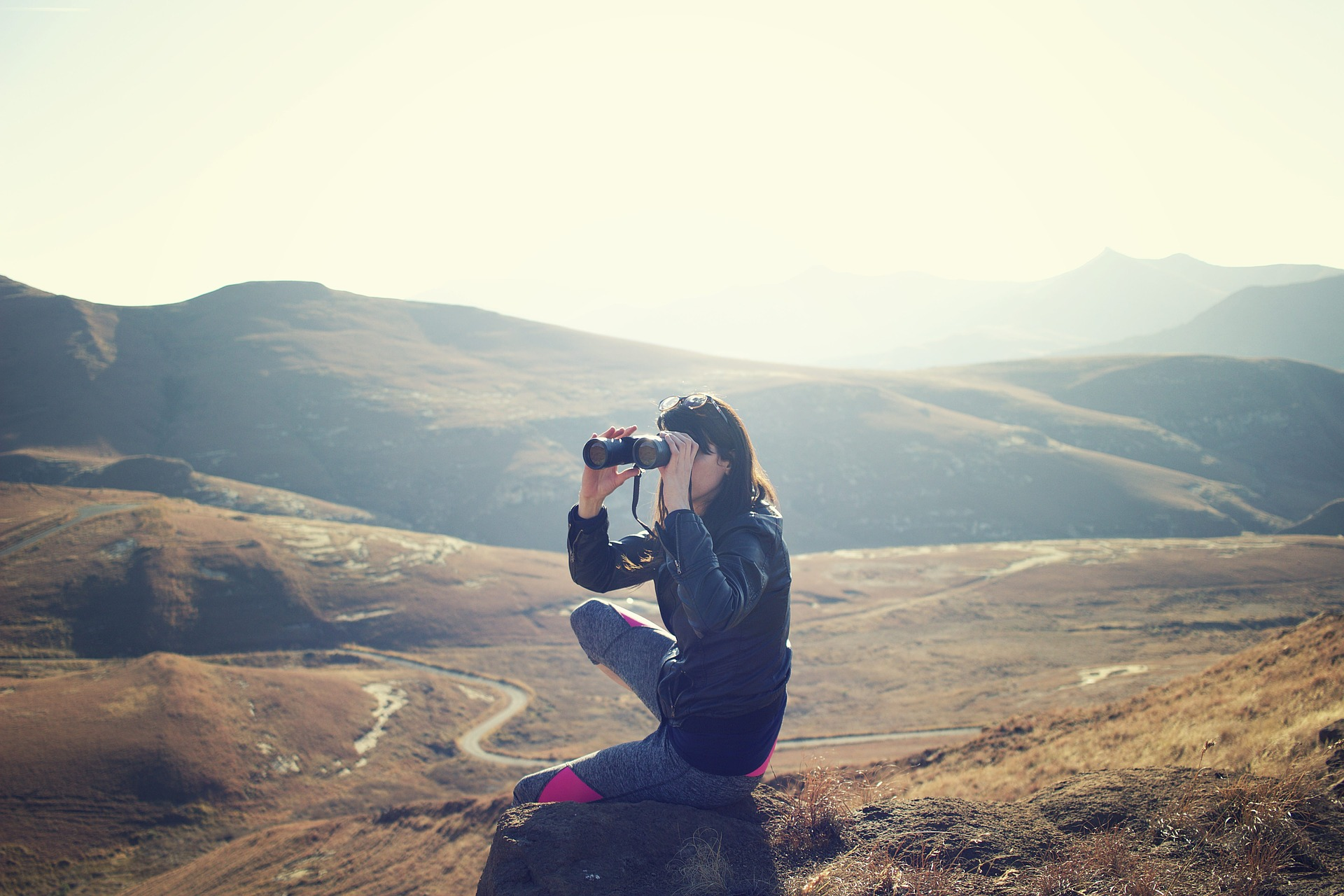 Woman on top of a mountain looking out over the scenery with binoculars