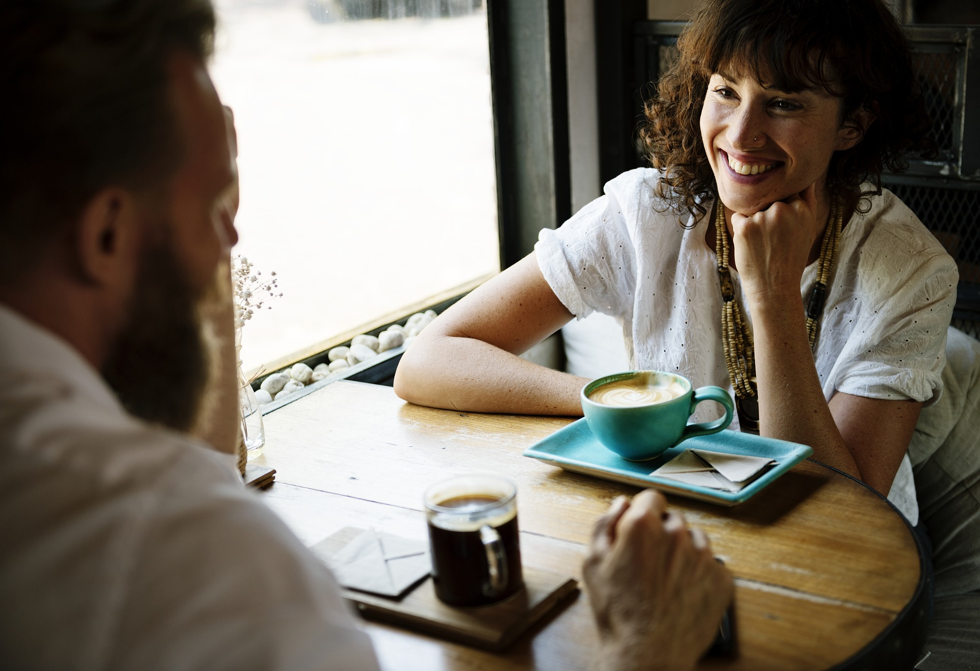 Man and a woman sitting having a coffee together in a cafe, woman is smiling