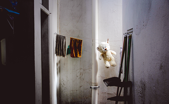 Washing on a clothesline in a laneway including a child's bear toy.