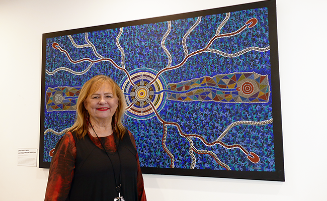 Elizabeth Crowther with an artwork by Heather Kamarra Shearer at the Wellways Fairfield office.