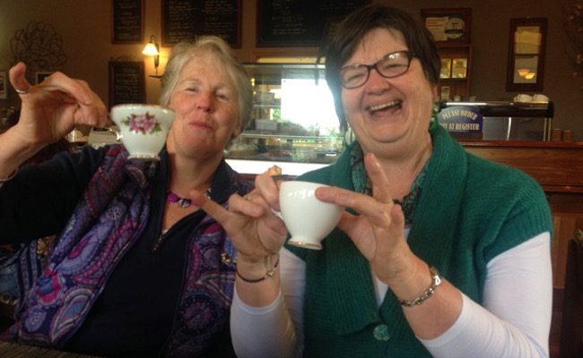 Beth and Michelle smiling and enjoying tea together
