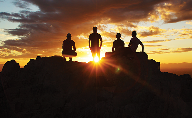 People standing on a mountain outlined by the sun setting