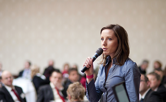 woman with a microphone speaking in front of a crowd
