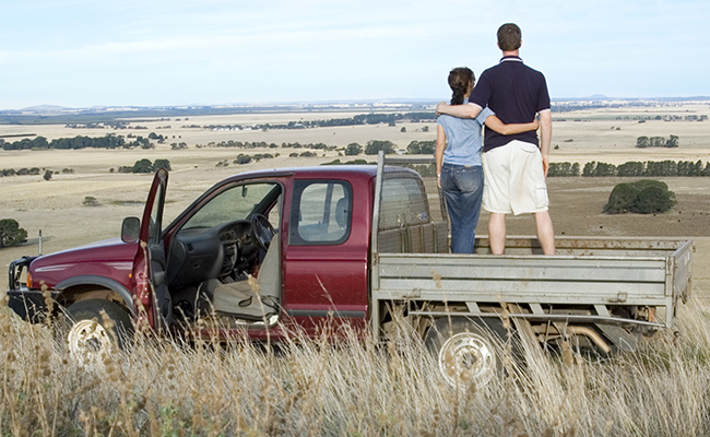 Two people standing on the back of a ute looking over farmland