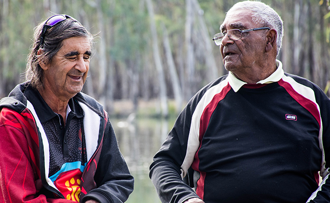 Two Aboriginal men talking and smiling