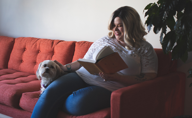 Woman sitting on a couch at home reading with her dog