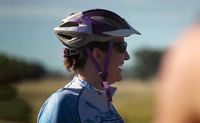 Woman wearing sunglasses and a bike helmet smiling