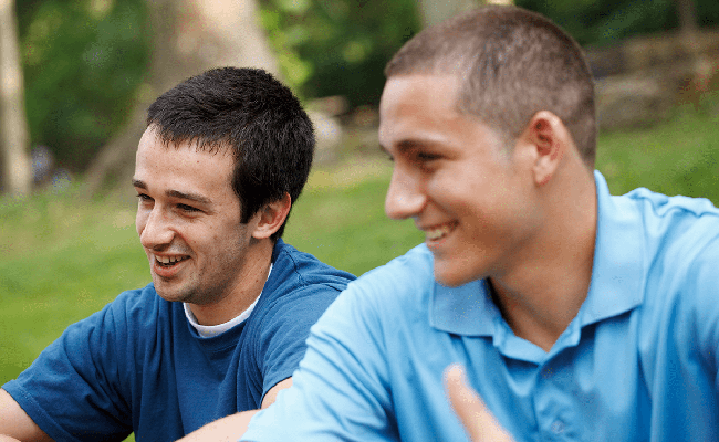 two boys sitting in a park smiling together