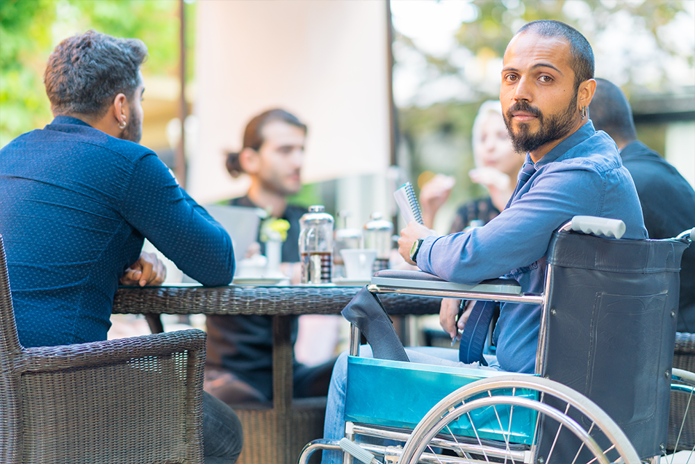 Man in a wheelchair holding a notebook and having coffee with friends