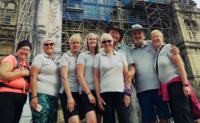 Group of Camino walkers standing in front of building under construction
